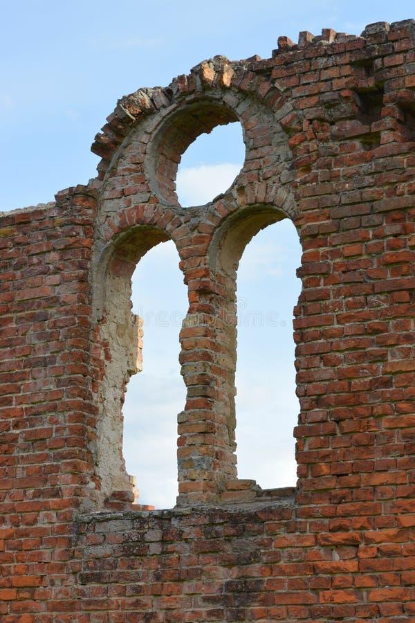 Janela do arco na parede de tijolo vermelho arruinada em um castelo antigo fotos de stock royalty free