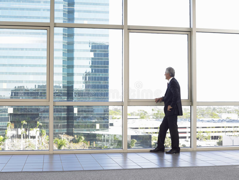 Janela do escritório de Looking Out Of do homem de negócios fotografia de stock