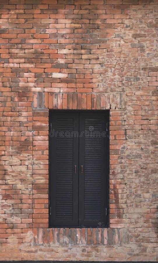 Janela do marrom escuro em uma parede de tijolo fotos de stock royalty free