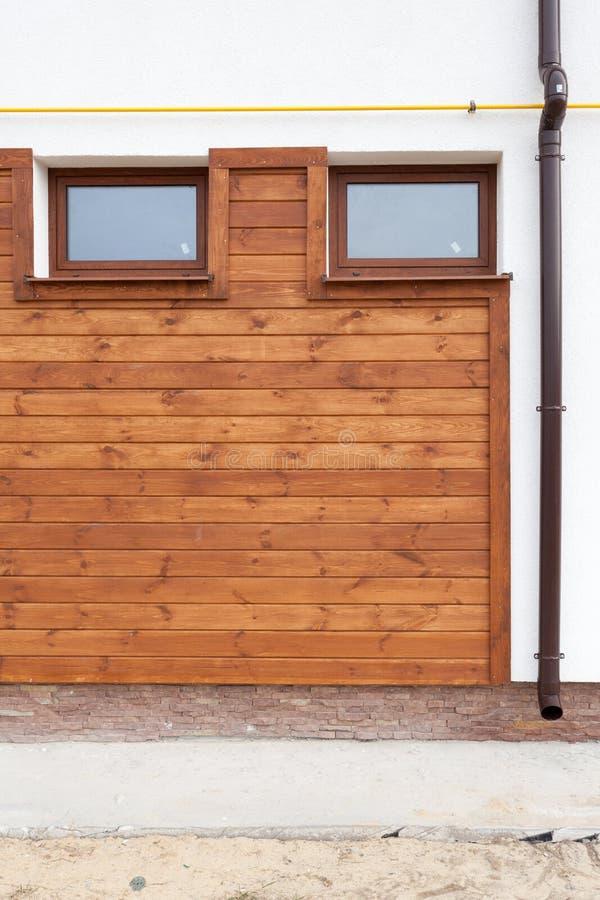 Janela do PVC e calha plásticas da chuva na parede de madeira passiva moderna nova da fachada da casa imagem de stock royalty free