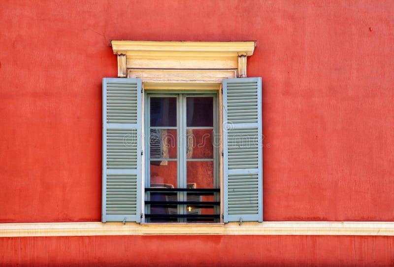 Janela do vintage com os obturadores cinzentos na casa vermelha velha do estuque, agradável, imagens de stock royalty free