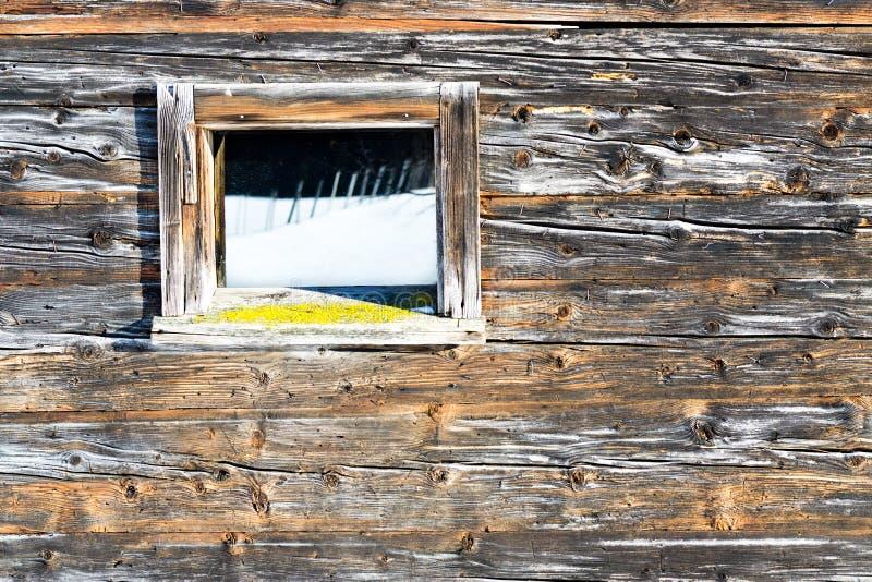 A janela do vintage da cabine de madeira velha espelha a paisagem do inverno Fundo rústico de madeira imagens de stock