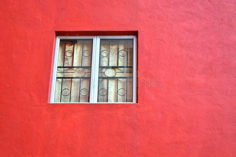 Janela em uma parede vermelha velha fotografia de stock