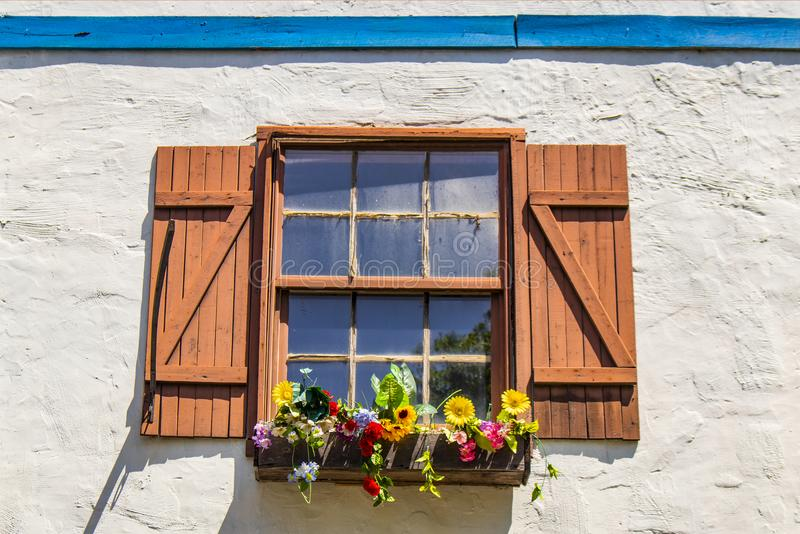Janela empoeirada colorida e do pictureque com obturadores e flores no windowbox com os obturadores na parede branca do estuque c fotografia de stock royalty free