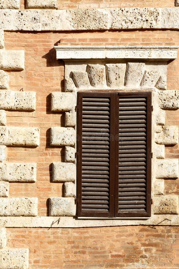 Janela europeia com os obturadores de madeira marrons em um tijolo interessante e em uma parede de pedra fotos de stock royalty free