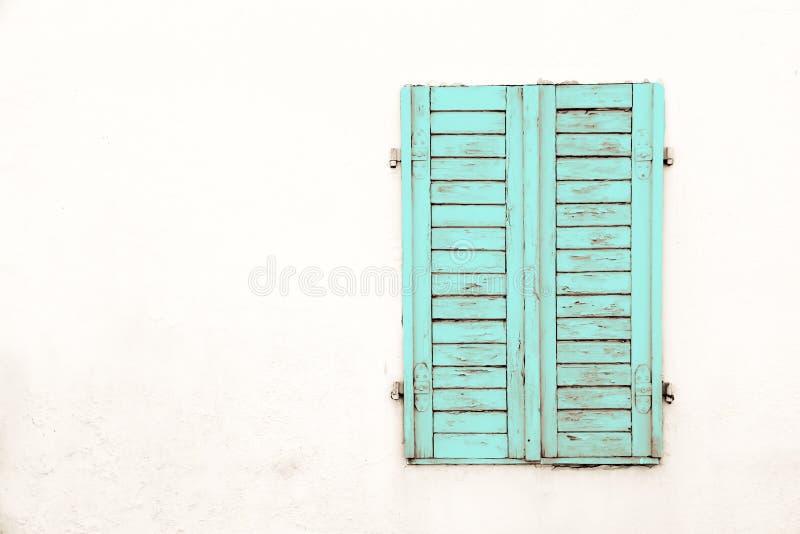 A janela fechado de madeira ciana verde suja e resistida velha rústica shutters com pintura da casca imagem de stock