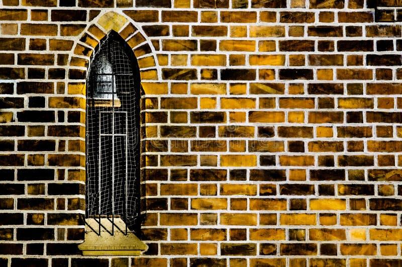 Janela gótico na parede de tijolo alaranjada imagens de stock royalty free