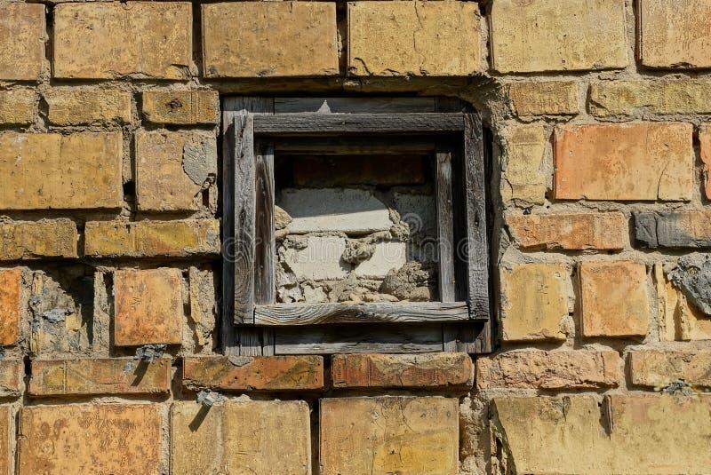Janela murada pequena velha na parede de tijolo da construção fotos de stock