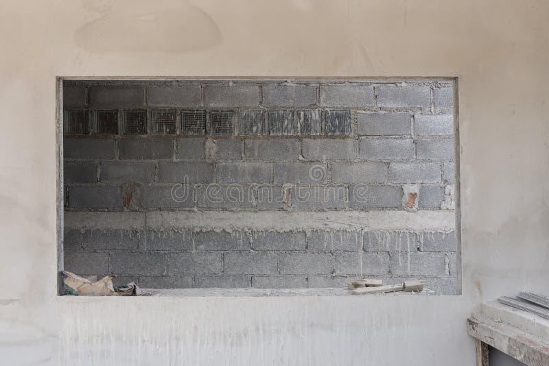 Janela na parede do cimento com fundo da parede de tijolo na construção imagens de stock royalty free