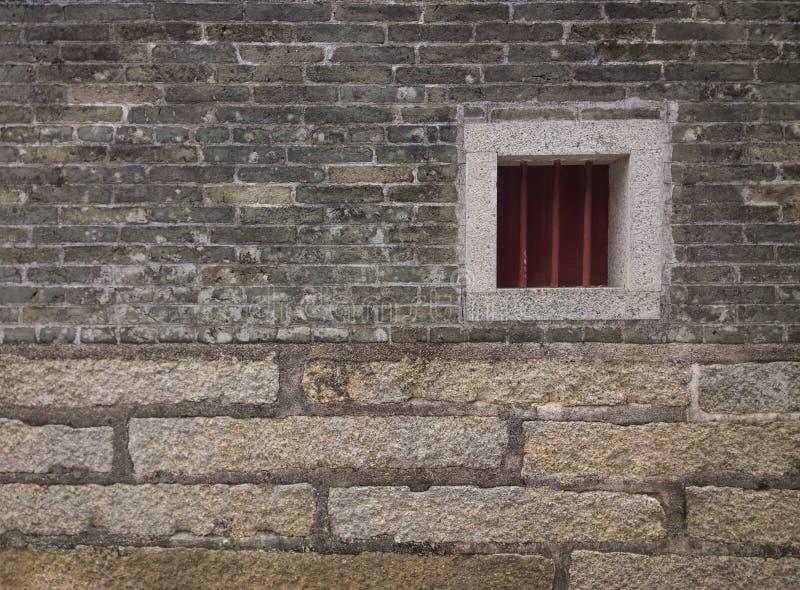 Janela pequena em uma parede de tijolo fotos de stock