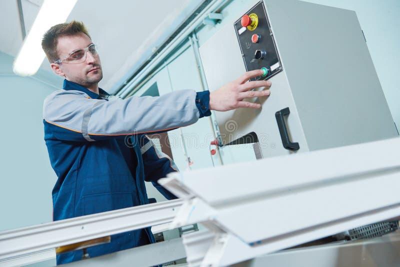 Janela plástica e fabricação da porta Trabalhador que corta o perfil do PVC imagem de stock