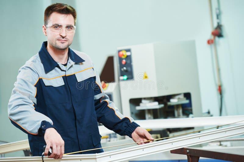 Janela plástica e fabricação da porta Trabalhador que corta o perfil do PVC foto de stock royalty free