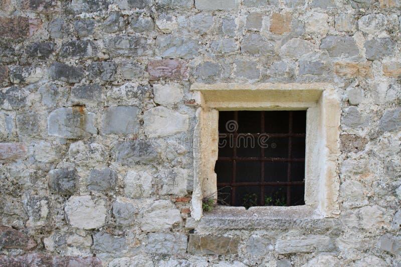 Janela quadrada velha com barras em uma parede de pedra fotos de stock