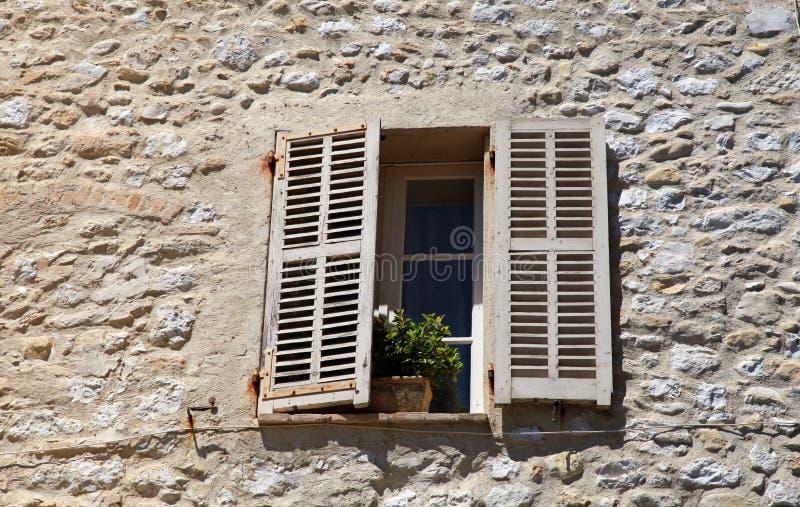 A janela rústica com os obturadores de madeira velhos na casa rural de pedra, prova fotografia de stock