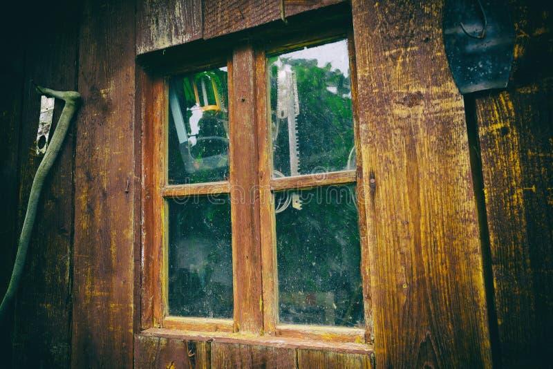 Janela suja e empoeirada em um celeiro de madeira velho, com as ferramentas de funcionamento atrás do vidro Feche acima da janela imagem de stock