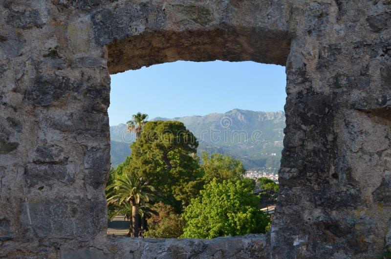 A janela velha da parede de pedra negligencia a aleia das palmeiras Montanhas no fundo fotos de stock royalty free