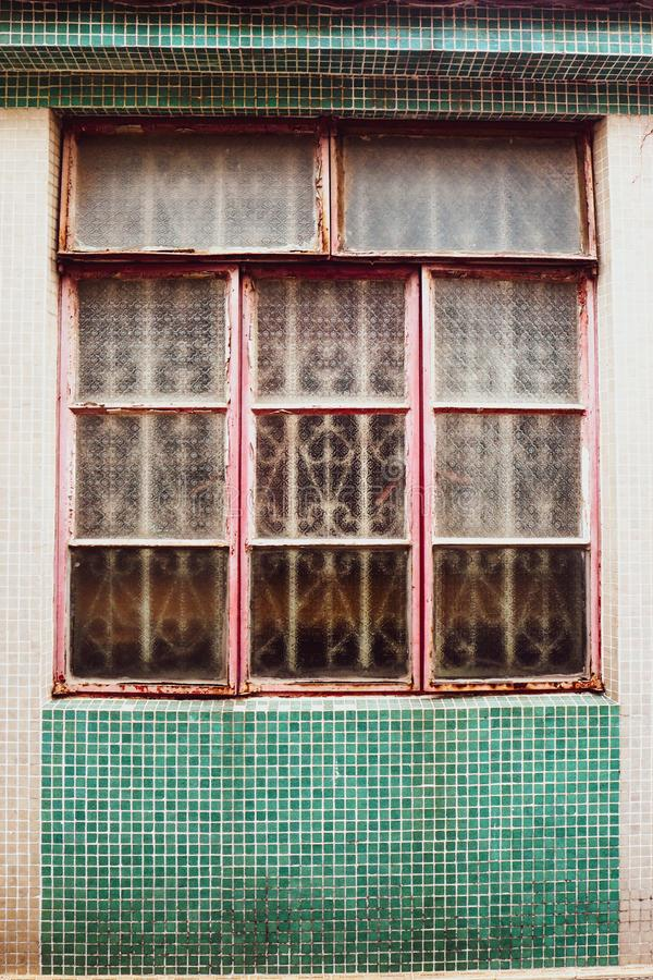 Janela velha do vintage do clássico velho do projeto da forma da casa no mosaico rústico verde no fundo do muro de cimento imagem de stock