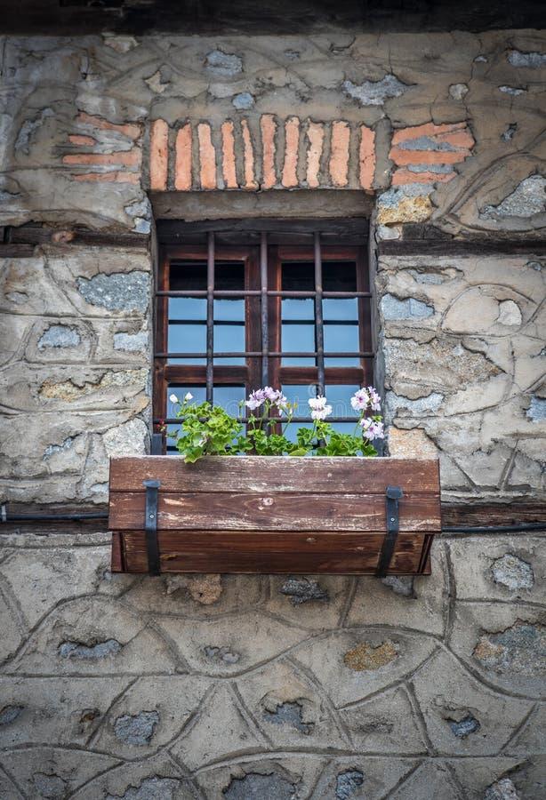 Janela velha do vintage com barras e flores de ferro no potenciômetro foto de stock royalty free