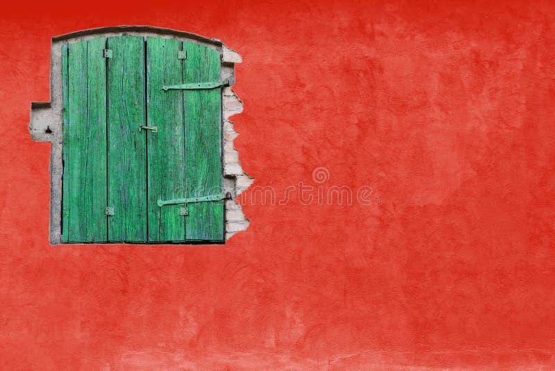 Janela verde na parede vermelha do estuque Fachada brilhante vívida da casa da casa da cor vermelha com a janela de madeira verde fotografia de stock royalty free