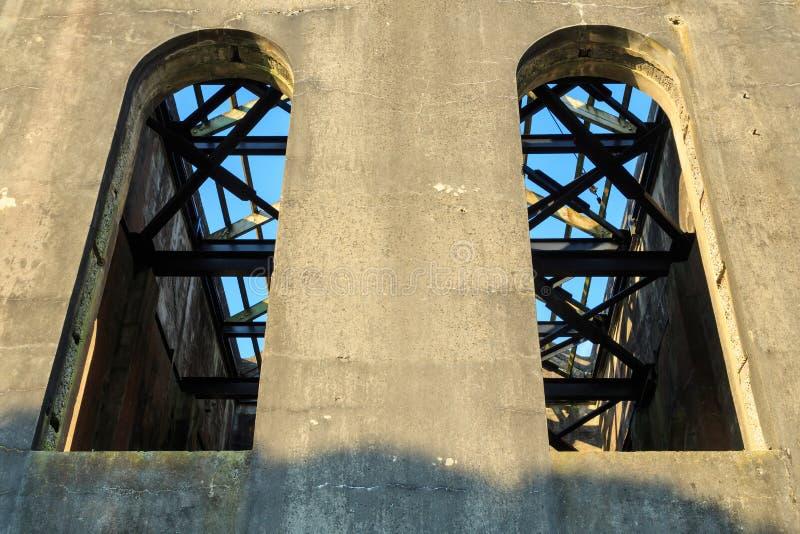 Janelas altas, arqueadas em uma construção industrial velha arruinada imagens de stock