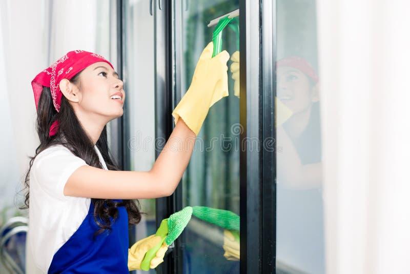 Janelas asiáticas da limpeza da mulher em sua casa imagens de stock