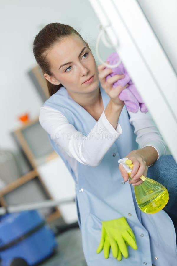 Janelas bonitas da limpeza da jovem mulher em casa imagens de stock