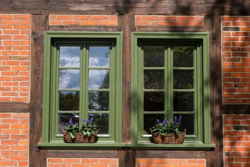 Janelas com quadros verdes e decoradas por flores em cestos imagens de stock royalty free