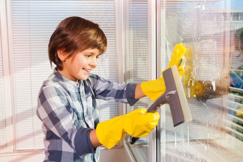 Janelas da limpeza do menino com o limpador da esponja e do vidro foto de stock royalty free