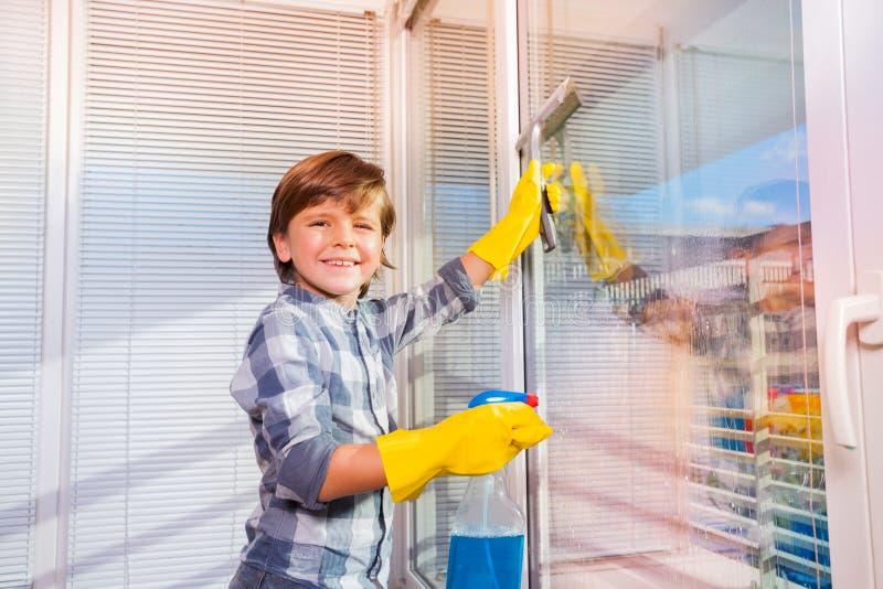 Janelas de lavagem de sorriso do menino com líquido de limpeza de janela imagens de stock