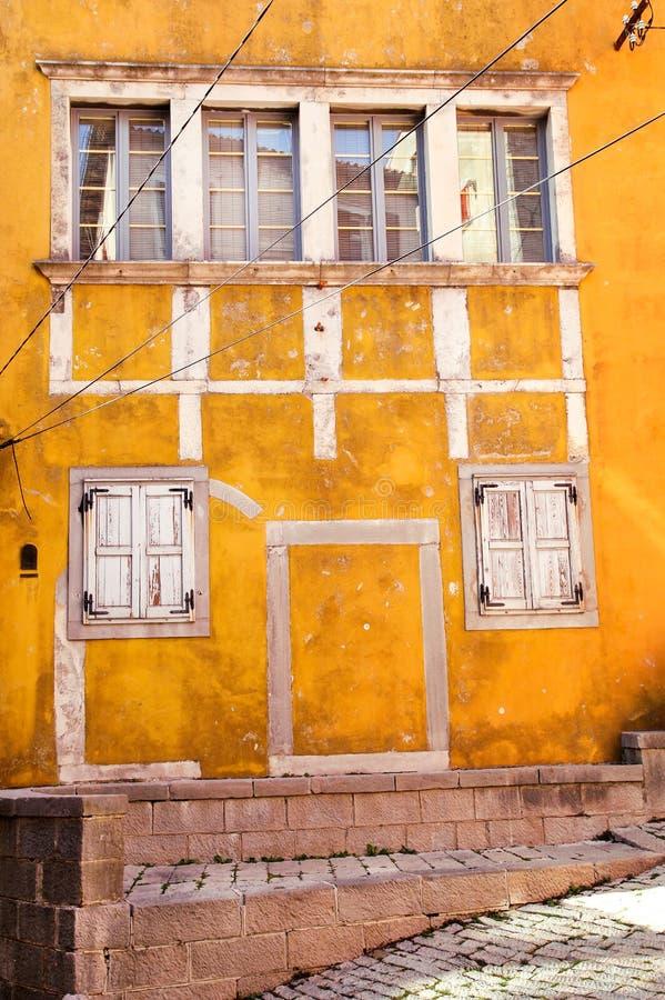 Janelas de madeira da fachada amarela velha/vintage clássico na construção concreta amarela/fundo arquitetónico imagem de stock royalty free