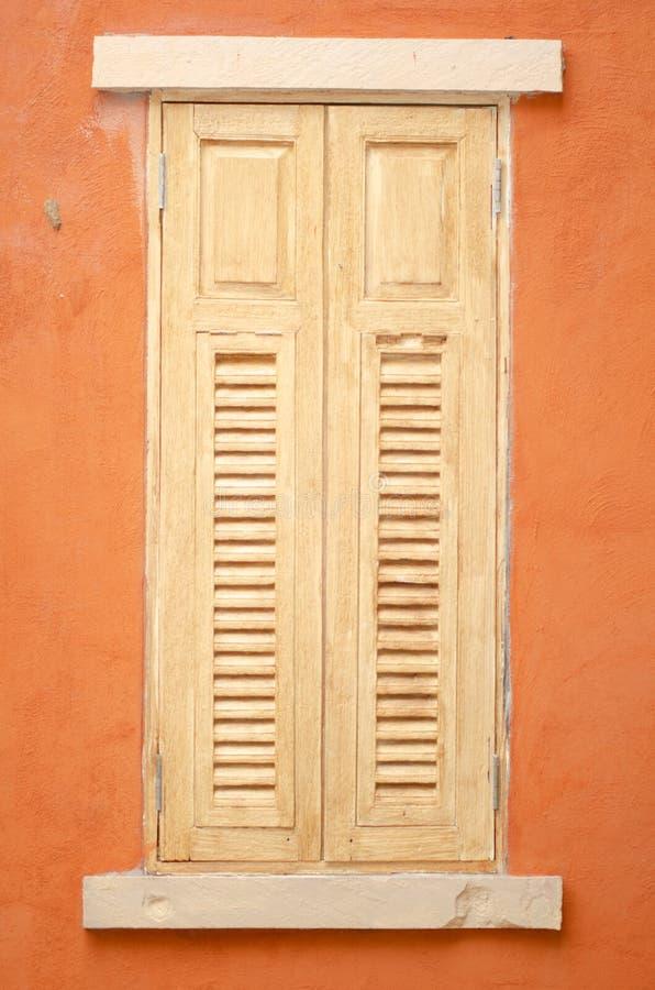 Janelas de madeira na laranja da cor do fundo imagens de stock