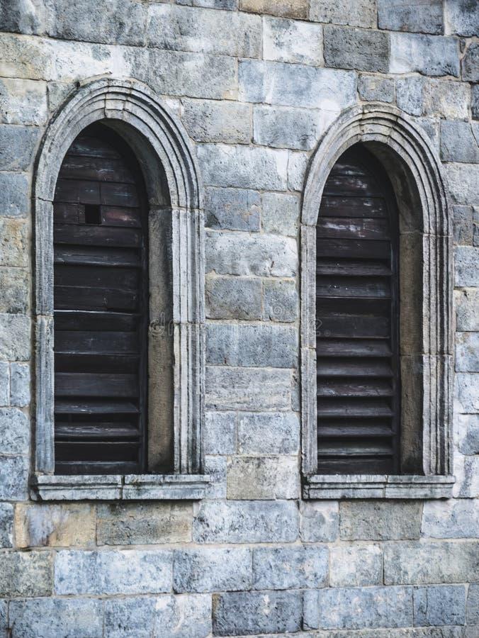 Janelas de madeira na parede do castelo fotografia de stock royalty free