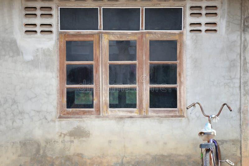 Janelas de madeira velhas na parede do cimento da casa e da bicicleta velha fotografia de stock
