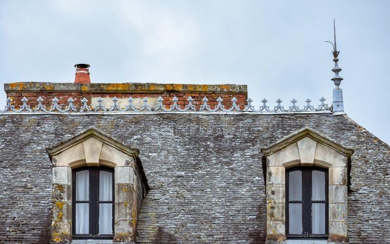 Janelas de trapeira no telhado de ardósia e em chaminés alaranjadas Rochefort-en-Terre, Brittany francês fotografia de stock