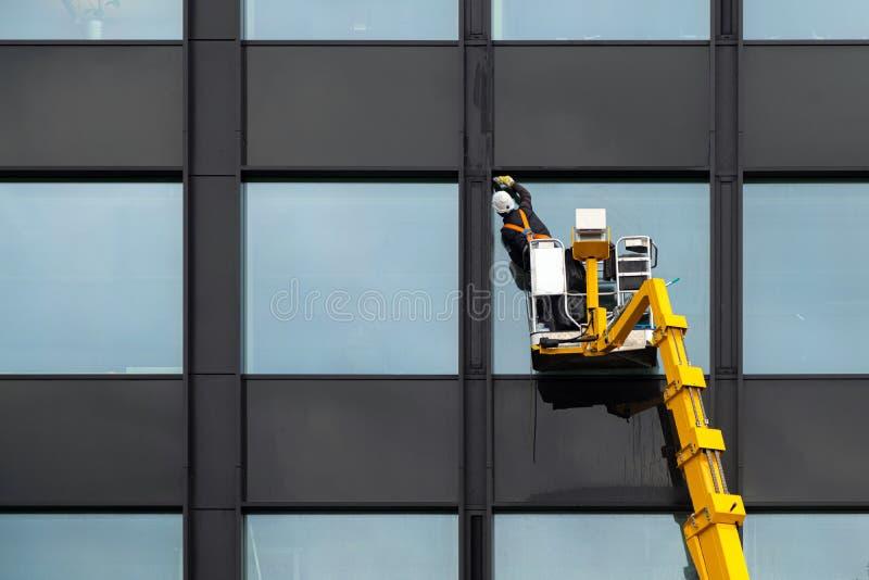 Janelas de vidro de limpeza masculinas de líquido de limpeza de janela na construção moderna alta no ar em uma plataforma do elev imagens de stock royalty free