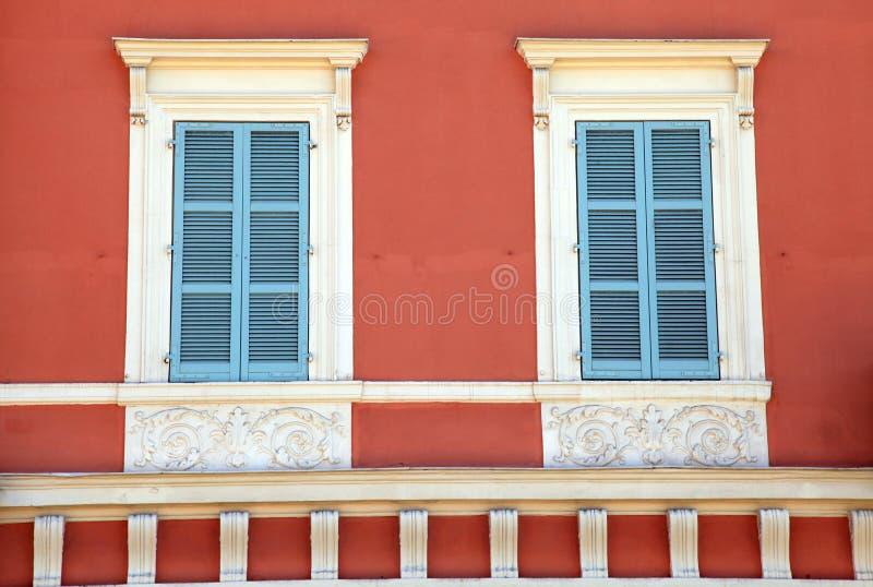 Janelas velhas do obturador do azul francês na casa vermelha, agradável, França. imagens de stock