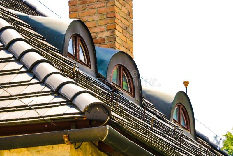 Janelas velhas do telhado no telhado de uma casa na parte velha da cidade foto de stock royalty free