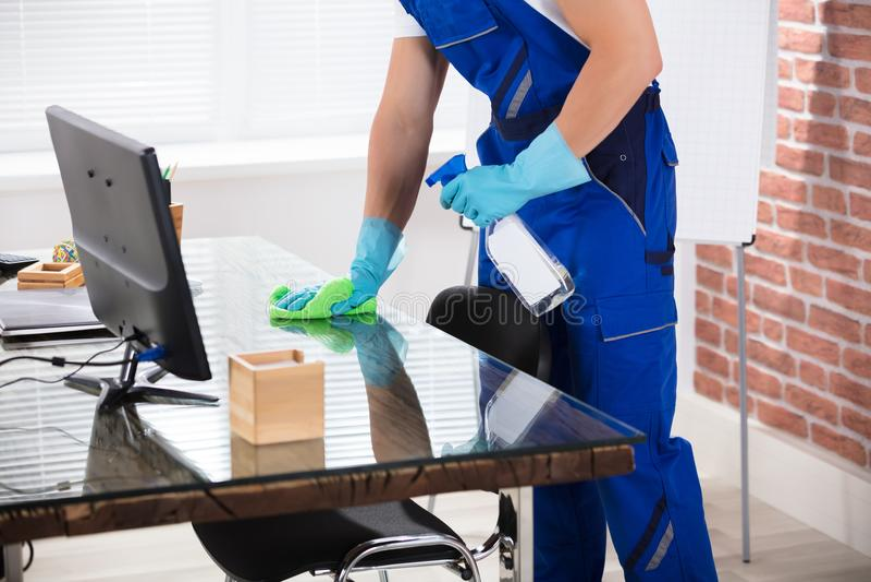 Janitor καθαρίζοντας γραφείο με το ύφασμα στην αρχή στοκ φωτογραφία με δικαίωμα ελεύθερης χρήσης