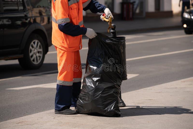 Janitor bierze grat z ulicznego łzawicy i stawia je w dużej czarnej torbie zdjęcia royalty free