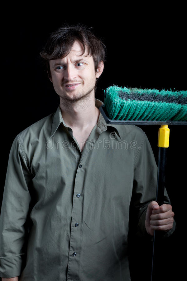 Janitor with a broom frowning at a mess. A man with a large push broom looks upset about the mess he has to clean up. Photographed in front of a black backdrop stock photography