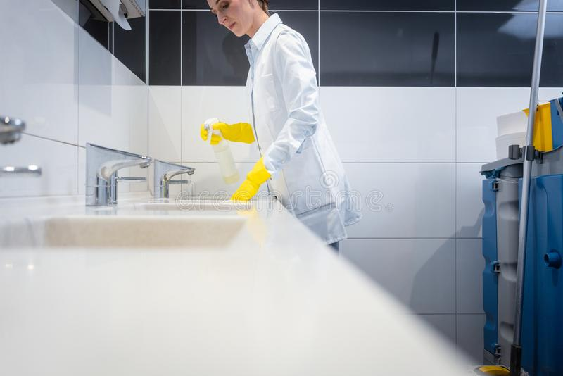 Janitor cleaning sink in public washroom. With cloth royalty free stock images