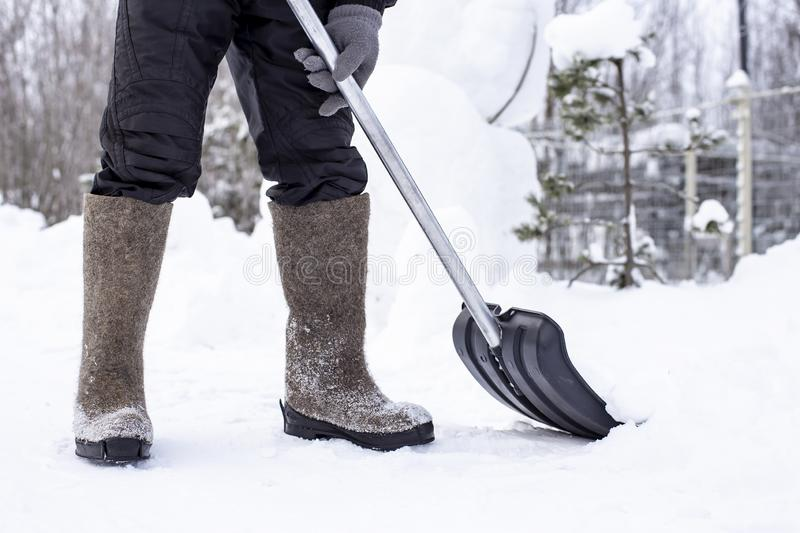 A janitor in felt shoes with a shovel clears a road in the countryside from a snowdrift, against a blurred background of a fence royalty free stock photo