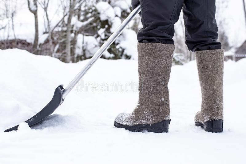 A janitor in felt shoes with a shovel clears a road in the countryside from a snowdrift, against a blurred background of a fence stock photos