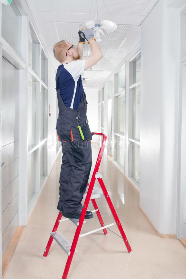 Janitor Fixing Broken Lamp stock image