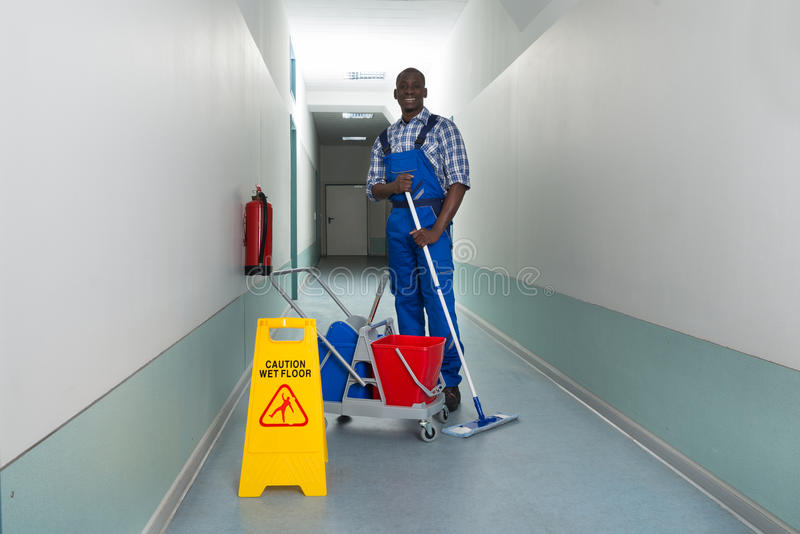 Janitor Holding Mop With Bucket And Wet Floor Sign Stock