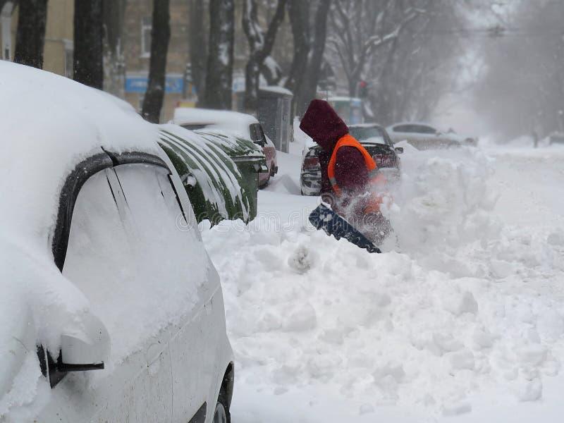 janitor I disastri naturali l'inverno, bufera di neve, forte nevicata hanno paralizzato la città, crollo Innevato il ciclone Euro fotografie stock