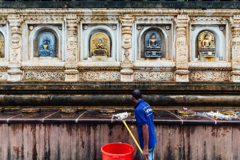 Janitor man cleaning wall of the temple that decorated with many forms and cultures of antique Buddha statues at Mahabodhi Temple. stock image