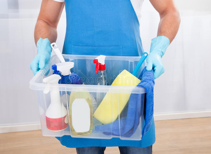 Janitor with a tub of cleaning supplies. Janitor or cleaner wearing an apron and gloves carrying a tub of cleaning supplies as he goes about his work at the stock photography