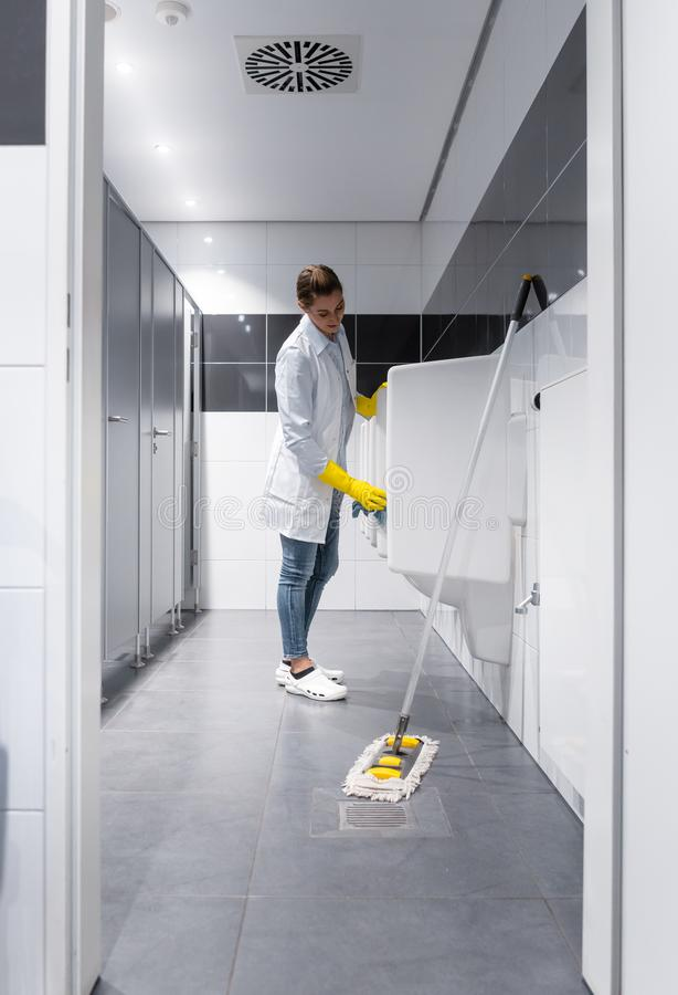 Janitor woman cleaning urinals in public toilet royalty free stock photos