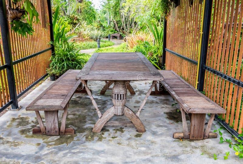 Jantando a tabela de madeira no jardim imagem de stock